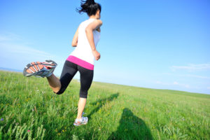 Runner athlete legs running on grass seaside